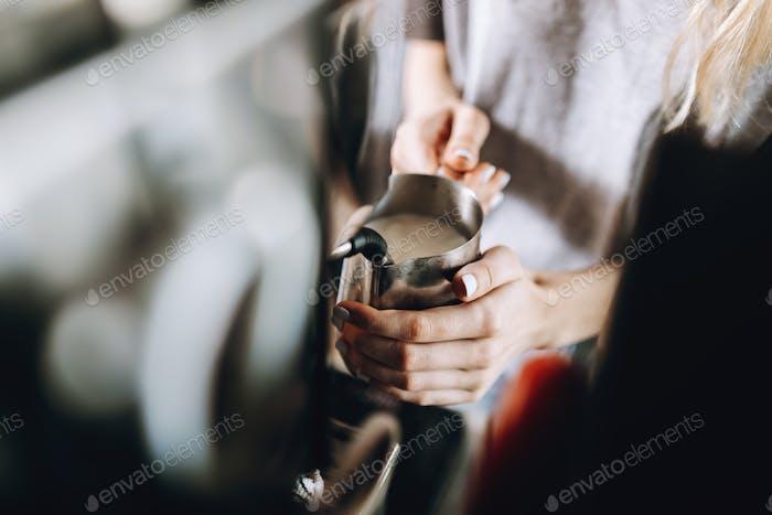 Una joven y delgada chica rubia, vestida con un atuendo casual, está sosteniendo un espumador de leche en un acogedor