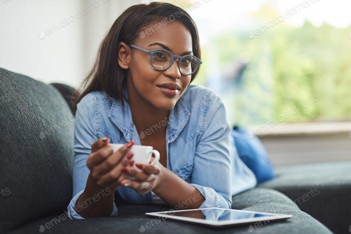 Junge Frau entspannt zu Hause mit einer Tablette und Kaffee