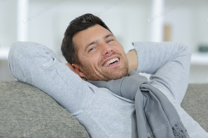 man smiling on sofa