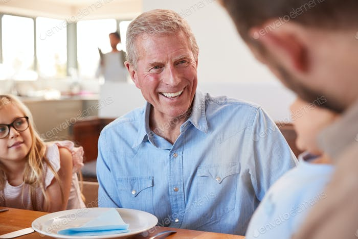 Multi-Generation Family Sitting Around Table Enjoying Meal At Home Together