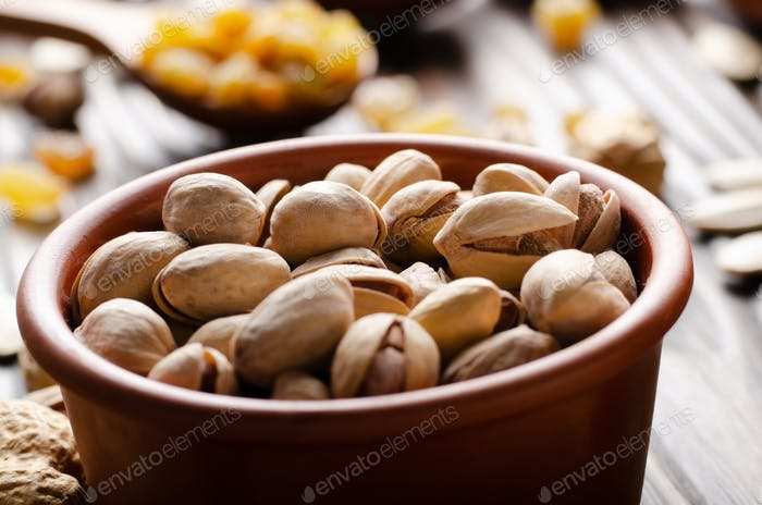 Pistazien Nüsse in Ton Schüssel auf Küche Holztisch Lebensmittel Hintergrund