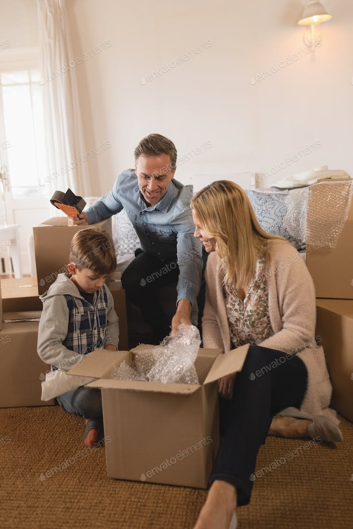 Front view of happy family in casual clothes unpacking cardboard boxes in their new home