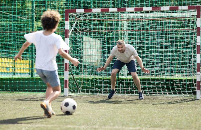 Kleiner Junge spielt Fußball, Kicking Ball zum Tor