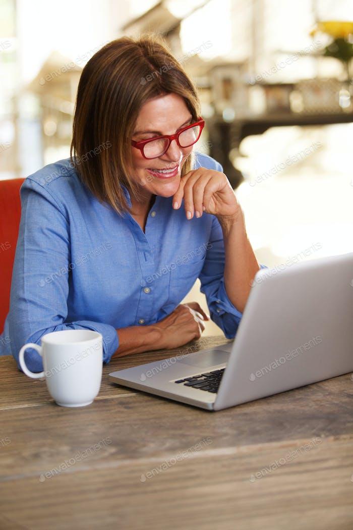 lächelnde Business-Frau sitzt am Schreibtisch arbeiten auf Laptop