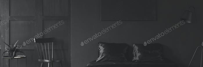 Header of a stylish black bedroom interior with a simple, wooden