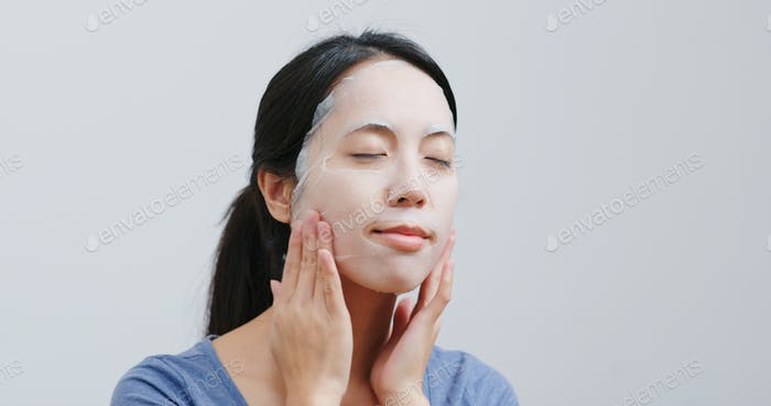 Woman apply face mask on face at home