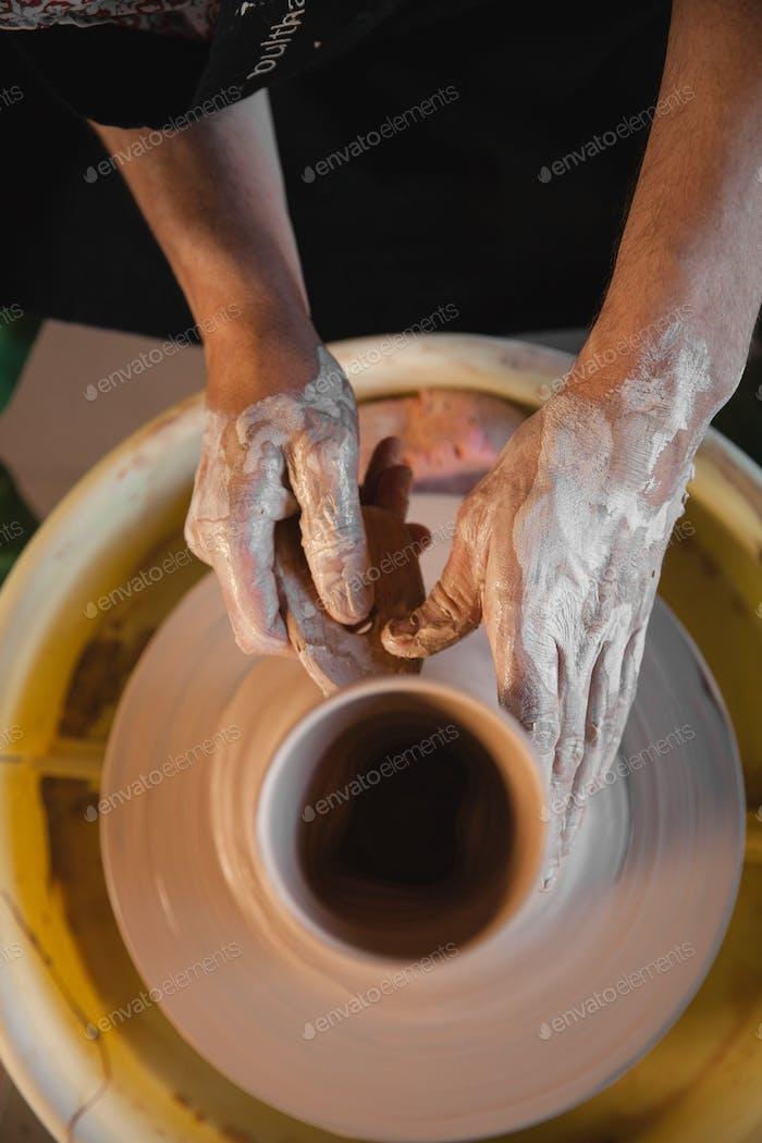 Unrecognizable potter master creating new ceramic bowl