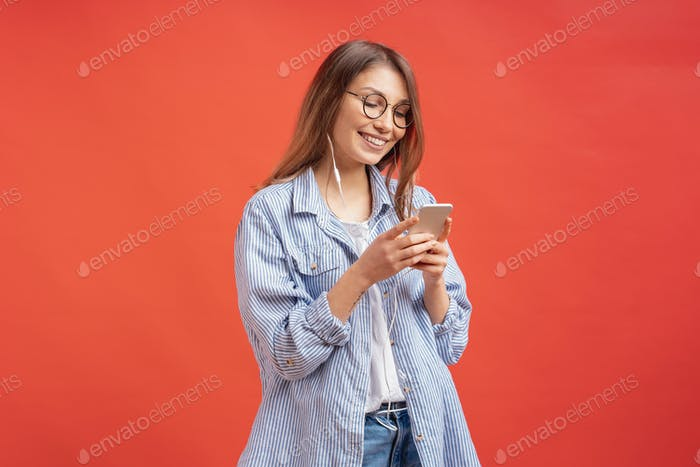 Smiling girl in casual clothes and earphones looking to phone screen