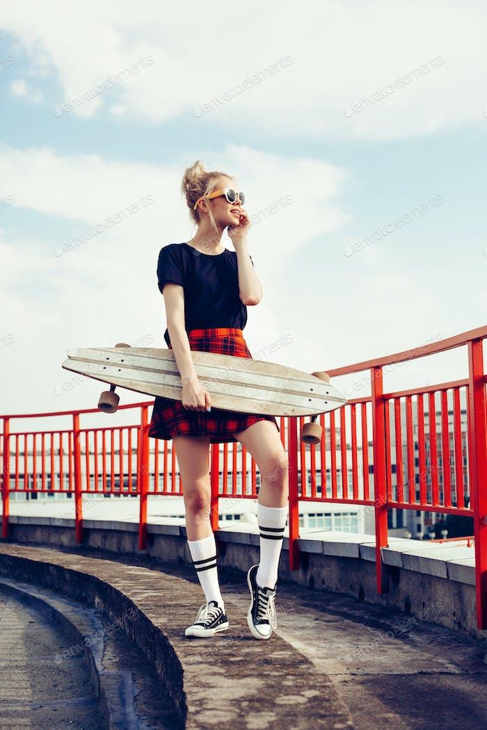 ziemlich sexy junge verführerische Frau mit longboard