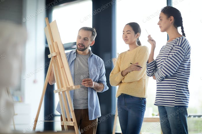 Students and teacher by easel