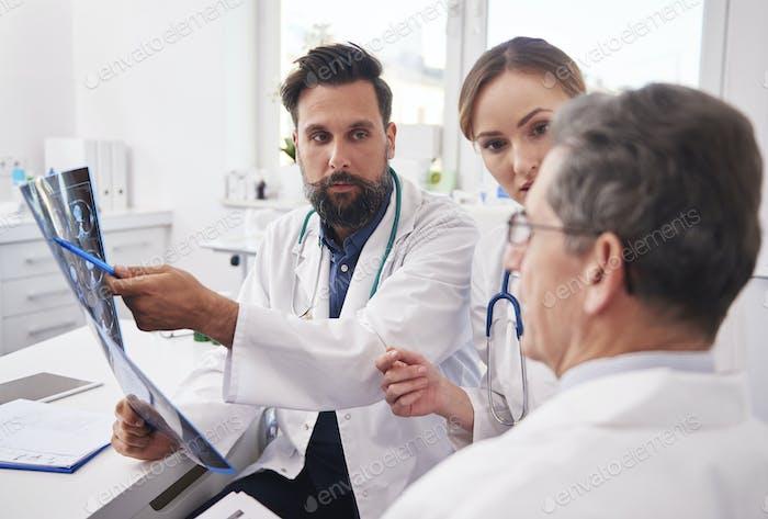 Gruppe von Ärzten, die sich die Ergebnisse der Radiologie ansehen