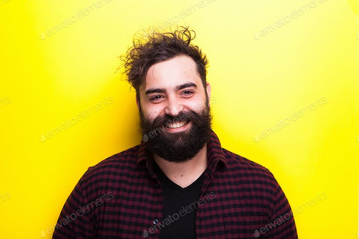 Happy smiling bearded hipster man on yellow background