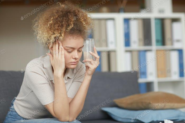 Woman drinking medicine from headache