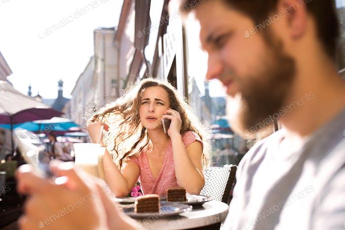 Joven pareja con teléfonos inteligentes sentado en el café.