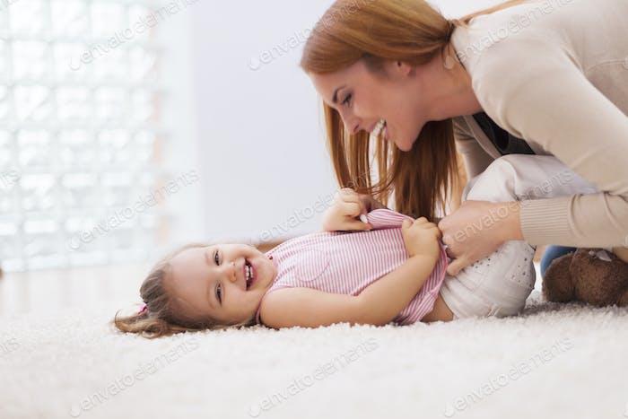 Loving mother tickling her little girl on carpet at home