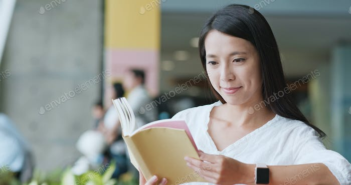 Woman read on book in university campus