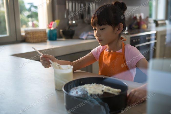Girl spreading cream on cake seen through glass