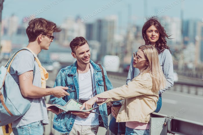 young tourists with backpacks and map traveling together