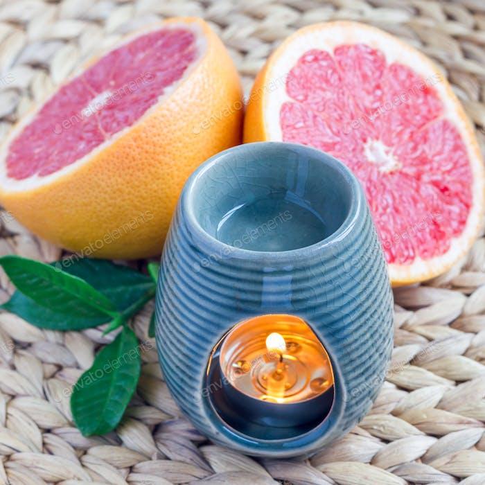 Aromalampe mit Grapefruitöl auf gewebter Matte, Grapefruits auf Hintergrund, quadratisch