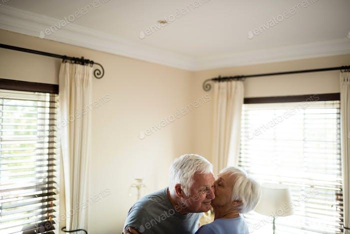 Seniorenpaar umarmen einander im Schlafzimmer
