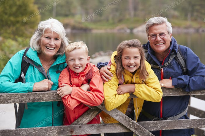 Grandparents and grandchildren leaning on a wooden fence in the countryside laughing