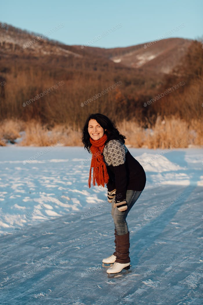 Happy woman ice skating on a frozen lake