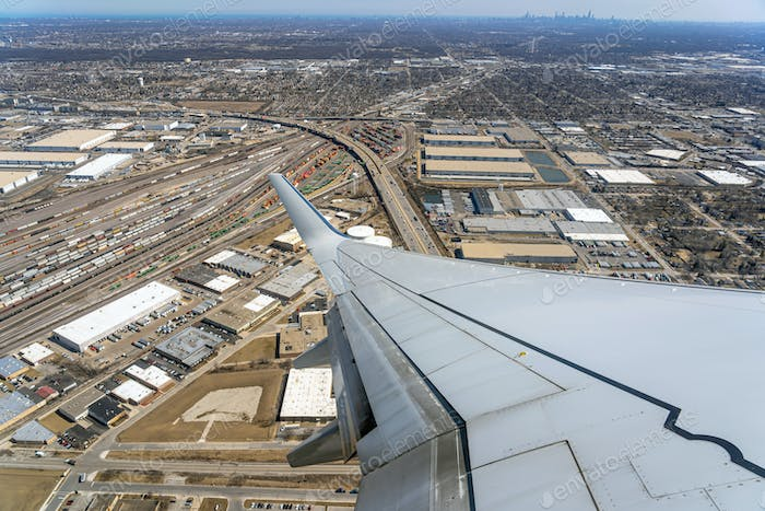 Aerial view of cargo trains and contrainers at the terminal railway which look through airplane