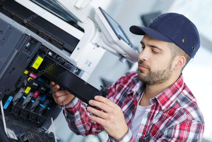 Mann Reparatur eines Druckers bei der Arbeit