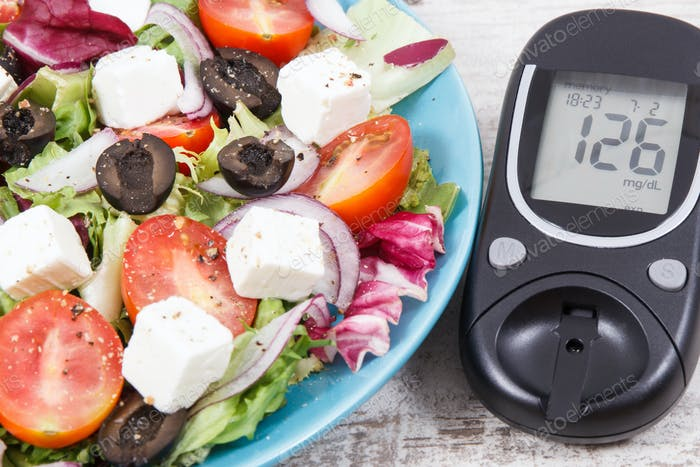 Glucose meter and fresh greek salad with feta cheese and vegetables