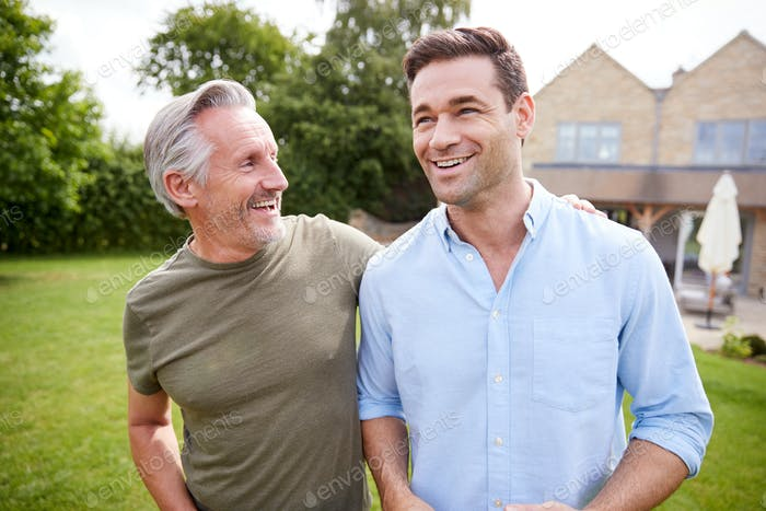 Senior Father And Adult Son Walking And Talking In Garden Together