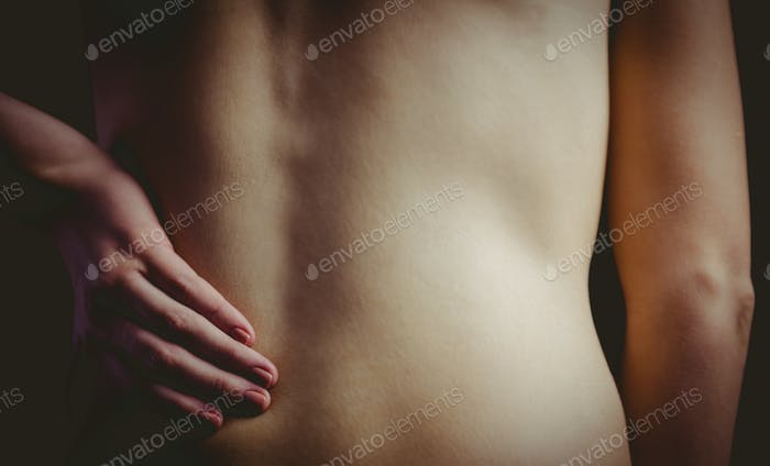 Nude woman with a back injury on black background