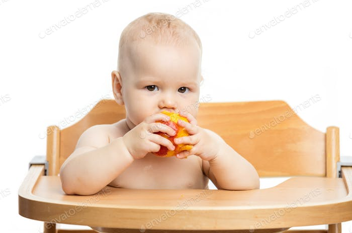 Cute baby girl eating peach while sitting in high chair over whi
