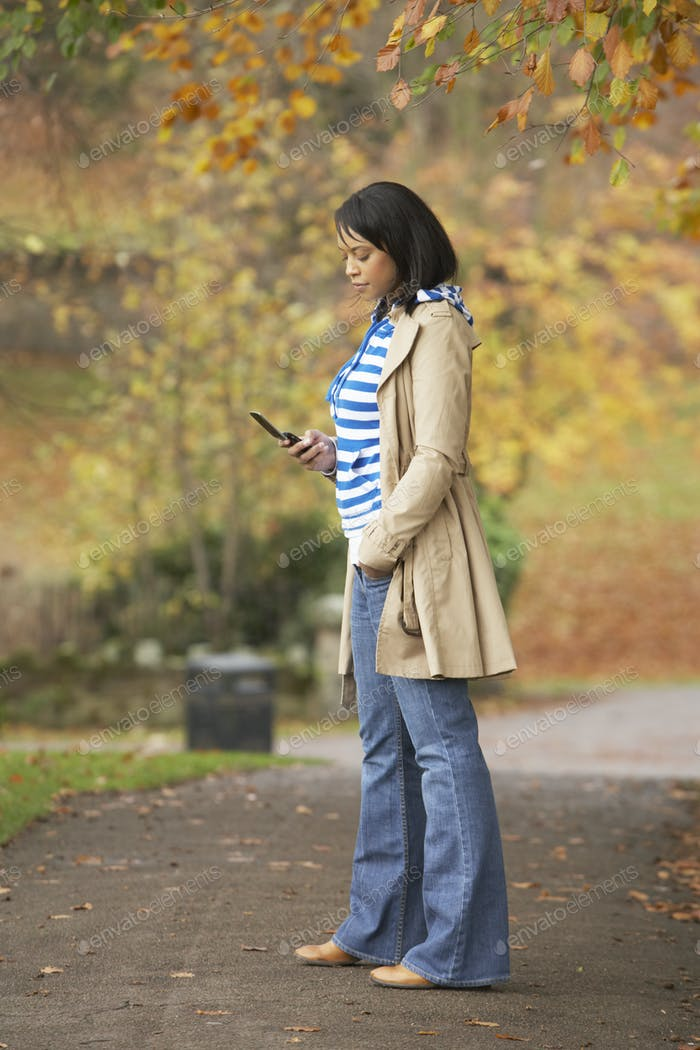 Teenage Girl Making Mobile Phone Call In Autumn Landscape