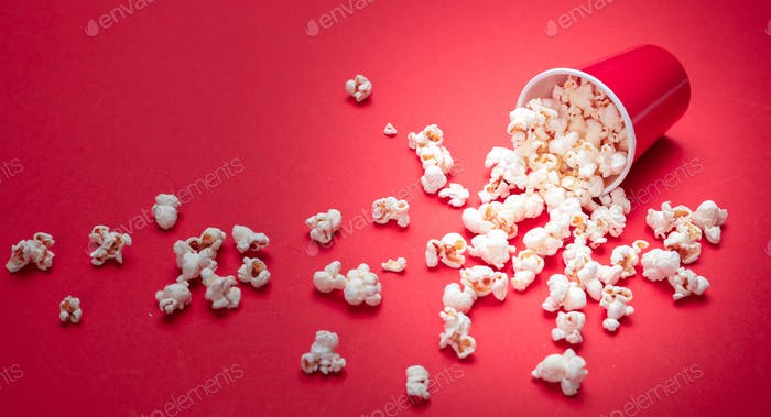 Pop corn scattered on red color background, closeup view