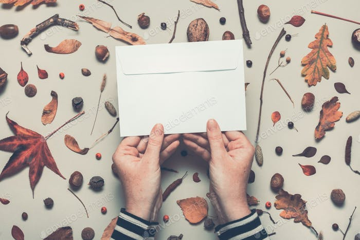 Woman holding blank post mail envelope mock up