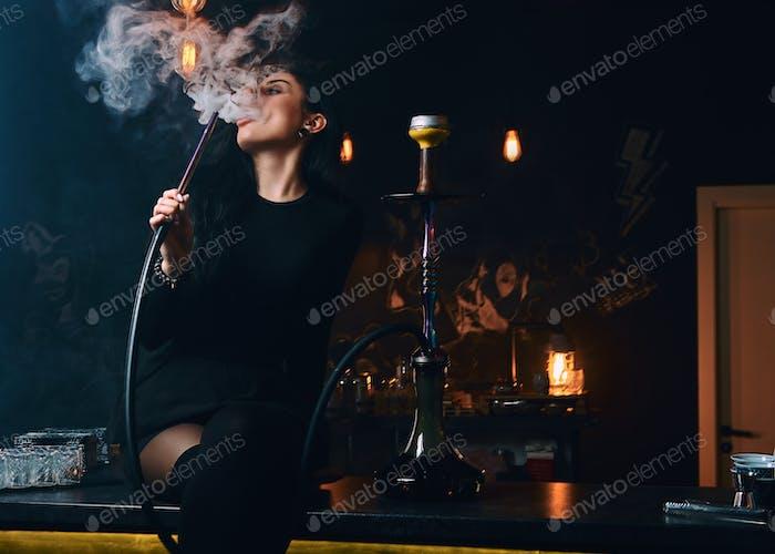 Seductive brunette girl in black clothes in a hookah