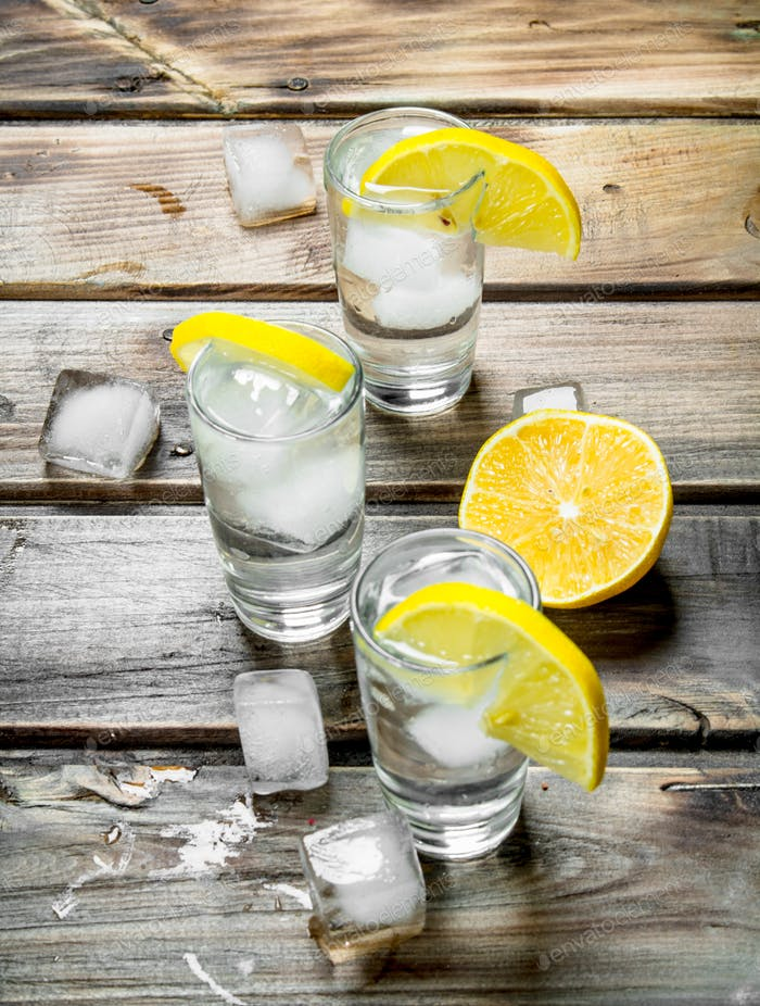 Vodka with ice in a shot glasses and slices of lemon.