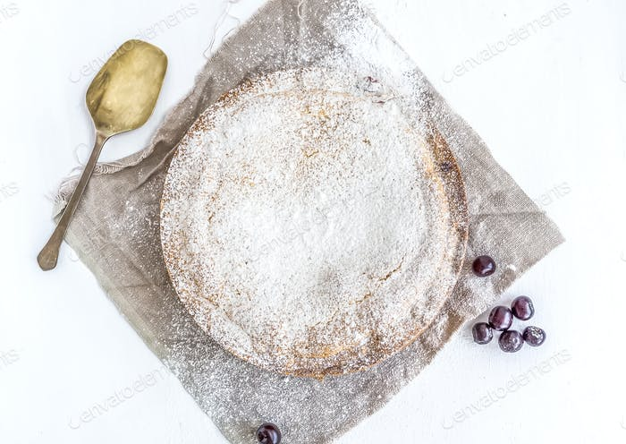 Custard cherry pie with fresh cherries  with a spoon on white