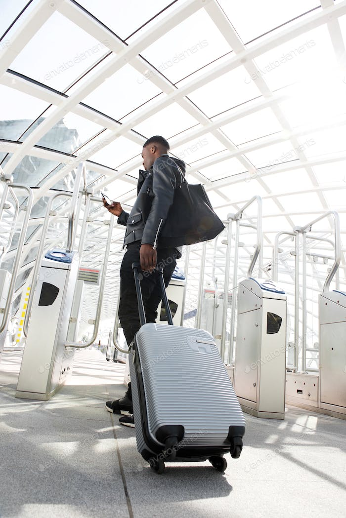 Full body young man traveling with suitcase and mobile phone at station