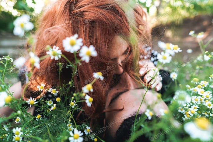 Young couple lies on the field with daisies