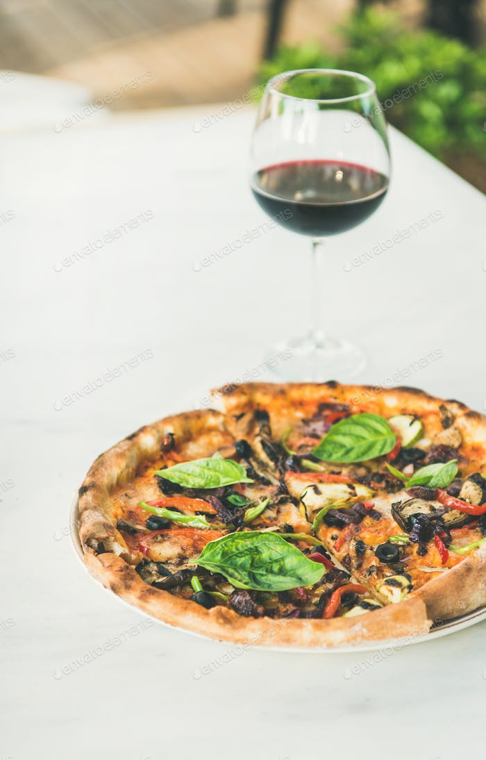 Freshly baked vegetarian pizza and glass of wine