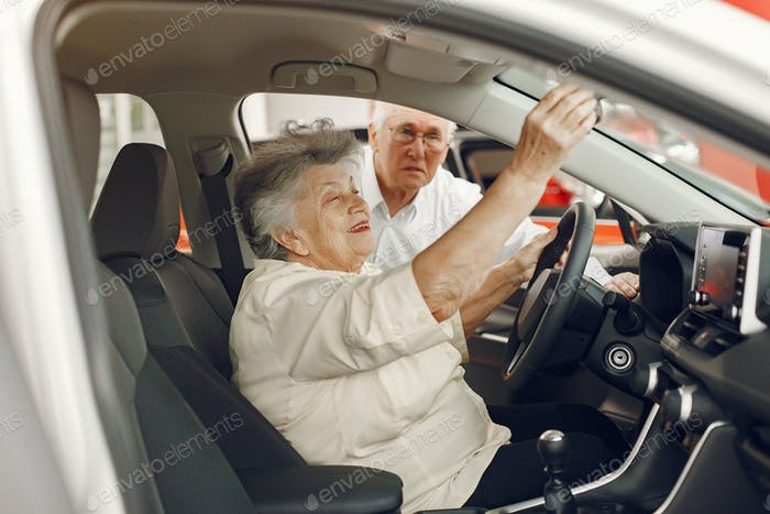 Elegant old couple in a car salon