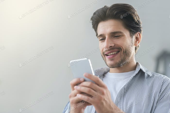 Cheerful millennial man texting with friend on cellphone