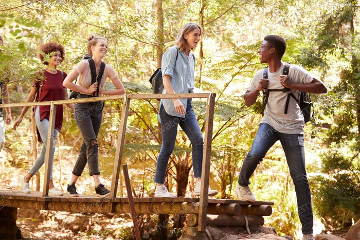 Young African American man turning to friends as they cross a footbridge during a hike in a forest