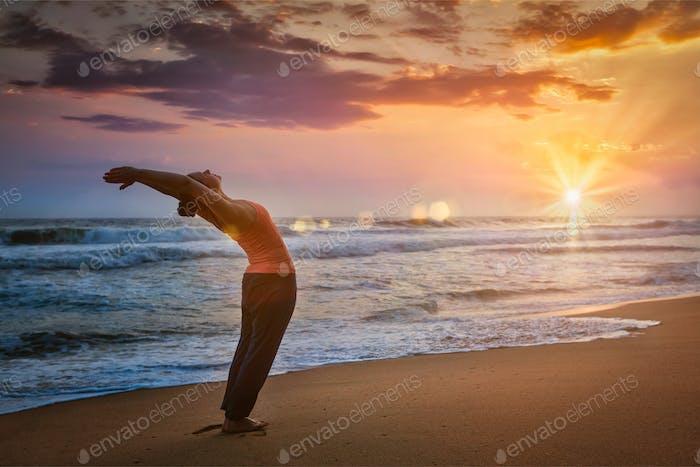 Junge sportlich fit Frau tun Yoga Sonne Gruß Surya Namaskar