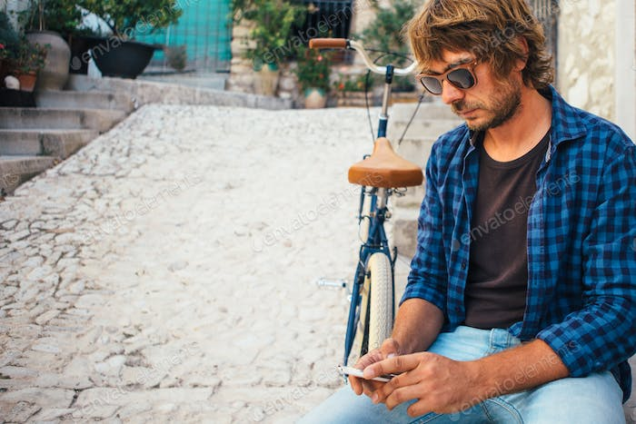 Young trendy man using phone