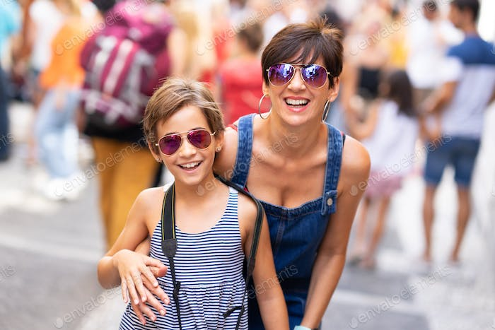 Mother and her little daughter traveling together in urban background