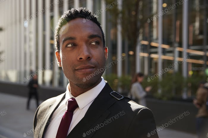 Young black businessman wearing black suit standing on the street smiling, looking away, close up