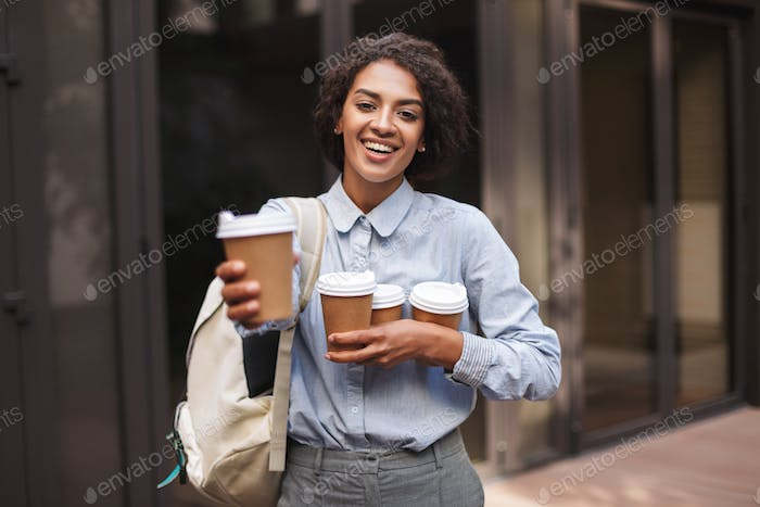 Young beautiful lady with dark curly hair standing with backpack and cups of coffee to go