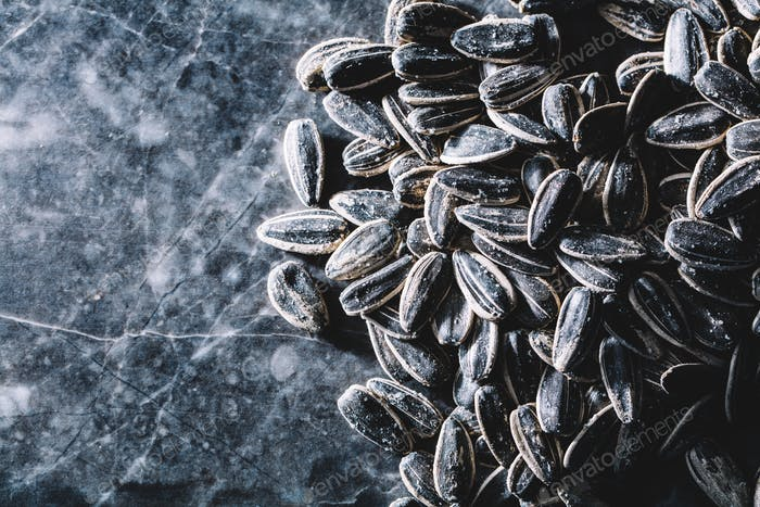 Black sunflower seeds on marble background